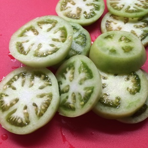 After preheating the oven to 400 degrees, I sliced my green tomatoes.